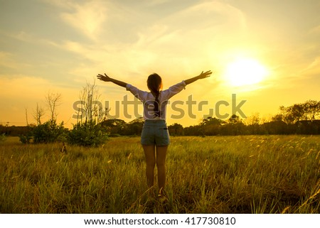 Young happy woman in meadow grass on sunset.