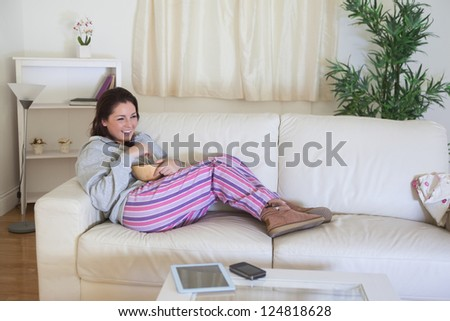Young happy woman in nightwear sitting on couch with bowl at home