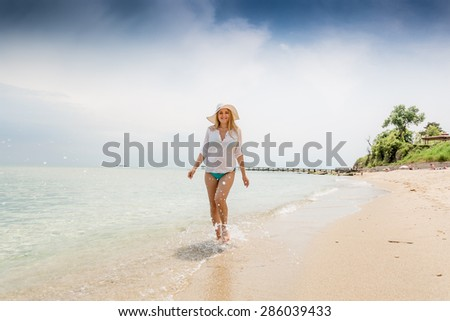 Young happy woman in shirt and hat walking in the sea waves on beach