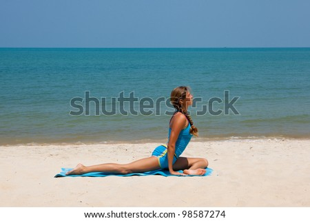 Young happy woman in the beach making yoga - stock photo