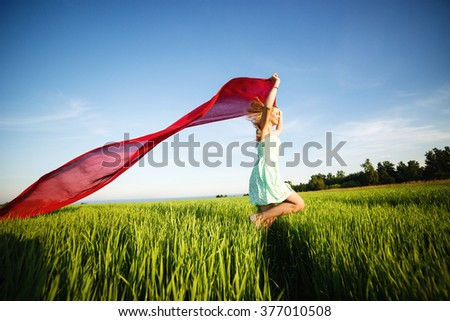 Young happy woman in wheat field with fabric. Summer lifestyle - stock photo