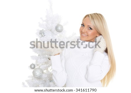Young happy woman in winter clothes stands near Christmas tree on a white background and holds an imaginary object in a hand. Free space for advertising of your product. - stock photo