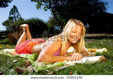 Young happy woman is reading a book on a meadow