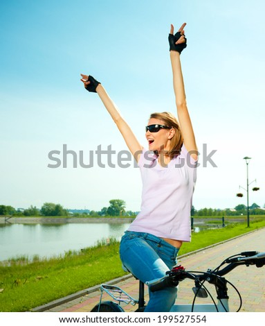 Young happy woman is sitting on her bicycle while raising hands up in joy, outdoor shoot - stock photo