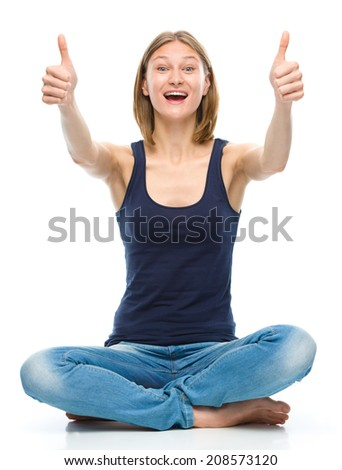 Young happy woman is sitting on the floor and showing thumb up sign using both hands, isolated over white - stock photo