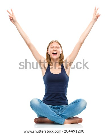 Young happy woman is sitting on the floor and showing victory sign using both hands, isolated over white - stock photo