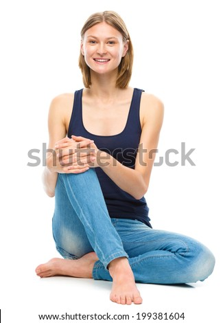 Young happy woman is sitting on the floor, isolated over white - stock photo