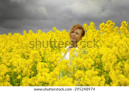 Young happy woman is walking in canola field under storm clouds - stock photo