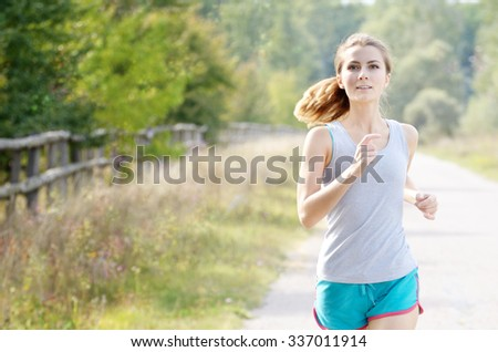 Young happy woman jogging on country road - stock photo