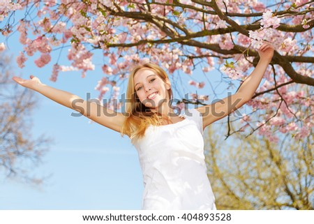 Young happy woman jumping in spring under a cherry blossom tree