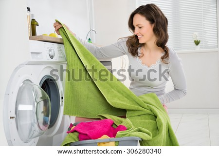 Young Happy Woman Laundering Clothes In Electronic Washer - stock photo