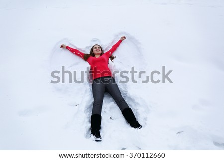 Young happy woman lies on snow,  top view - stock photo