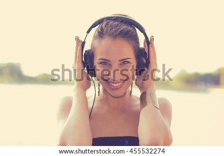Young happy woman listening to music on headphones outdoors by the lake  - stock photo