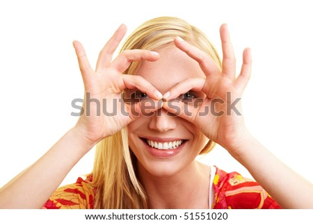 Young happy woman looking through a hole in her fingers