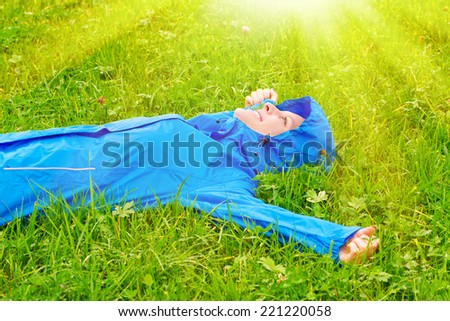 Young happy woman lying on meadow - stock photo