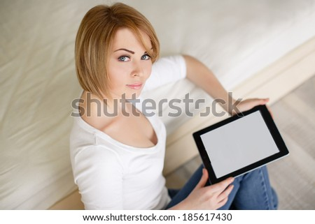 Young happy woman lying on the floor with pillows and using tablet computer at home - stock photo