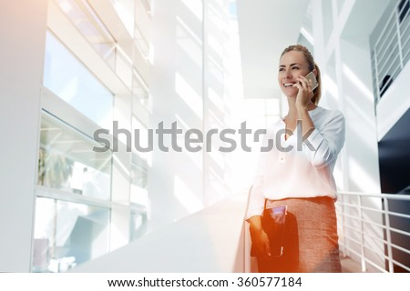 Young happy woman manager talking on smart phone with her boss about successful meeting with clients, smiling female prosperous employed calling with cell telephone while standing in office interior  - stock photo