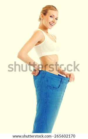 Young happy woman measuring waist with a tape measure in old jeans, health and dieting concept - stock photo