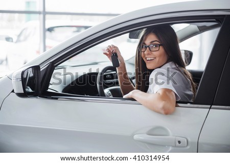 Young happy woman near the car with keys in hand - concept of buying car - stock photo