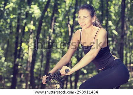 Young happy woman on bike standing on a hill road enjoying beautiful summer sunny day resting relaxing making a pause after a long trip