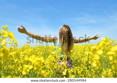 Young happy woman on blooming rapeseed field in spring - stock photo