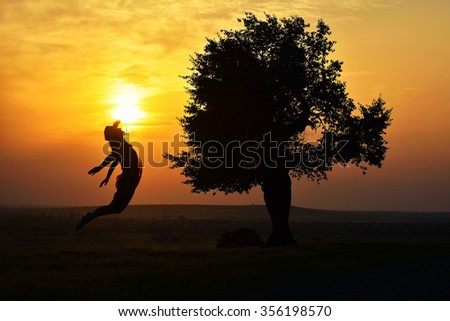 young happy woman on field in summer sunse