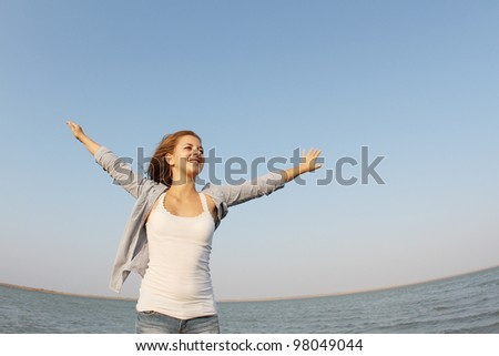 young happy woman on sea and sky background - stock photo