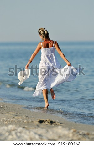 young happy woman on the beach in summer sunny day