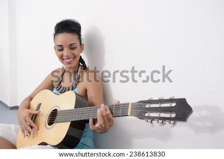 Young happy woman playing guitar - stock photo
