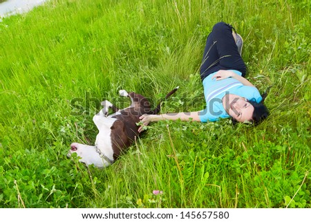 Young happy woman playing on the grass with her dog - stock photo