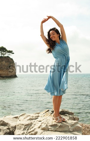 Young happy woman posing near sea, summer vacation