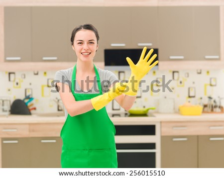 young happy woman putting rubber gloves and getting ready for cleaning - stock photo