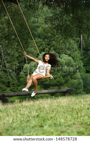Young happy woman riding on a swing in the park
