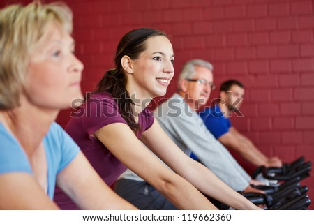 Young happy woman riding spinning bike in a fitness center - stock photo