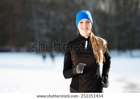 Young happy woman running during winter