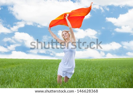 Young Happy Woman Running In Field Holding A White Piece Of Cloth