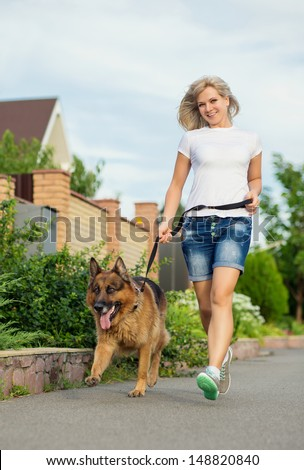 Young happy woman running with her dog  - stock photo