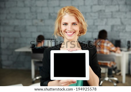 Young happy woman showing blank tablet computer screen in office - stock photo