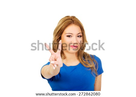 Young happy woman showing victory sign. - stock photo
