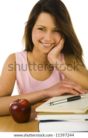 Young happy woman sitting at desk. Looking at camera. On the desk lying books and red apple. Front view. White background.