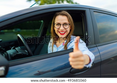 Young happy woman sitting in a car with thumb up - concept of buying a used car or a rental car