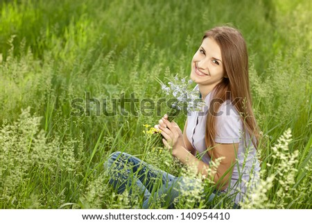 Young happy woman sitting in grass with bunch of wild flowers