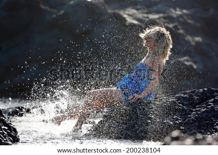 young happy woman sitting on rocky beach in summer - stock photo