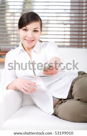 young happy woman sitting on sofa with remote control