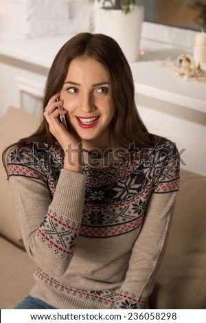 Young happy woman sitting on the sofa at home while talking on phone - stock photo