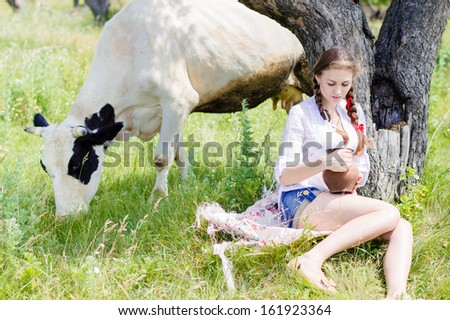 Young happy woman sitting tired near cows in countryside on summer day