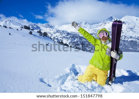 Young happy woman skier hugging her ski and waving hand with mountains on background - stock photo