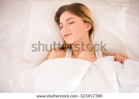Young happy woman sleeping in bed at home - stock photo
