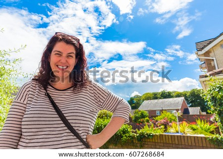 Young happy woman standing in her garden outside her home
