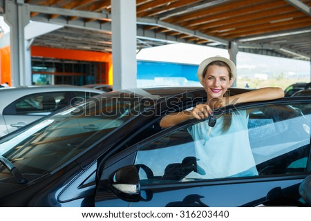 Young happy woman standing near a car with keys in hand - concept of buying a used car